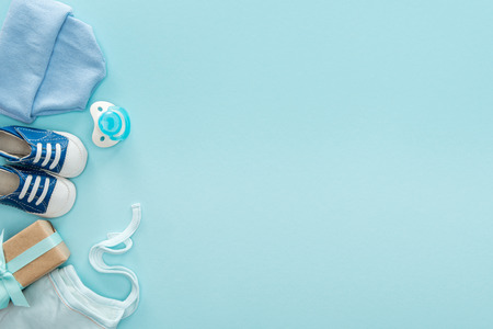 top view of pacifier, gift, sneakers, bonnet, hat on blue background with copy space 스톡 콘텐츠