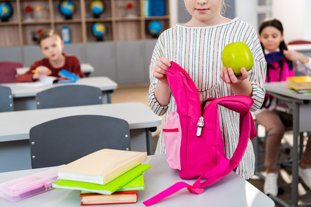 Cropped view of schoolgirl holding green apple and pink backpack in classroom