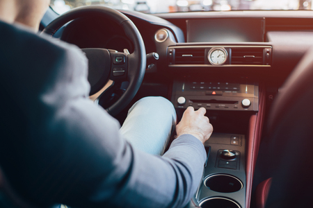 cropped view of man sitting in modern automobile and holding manual transmission