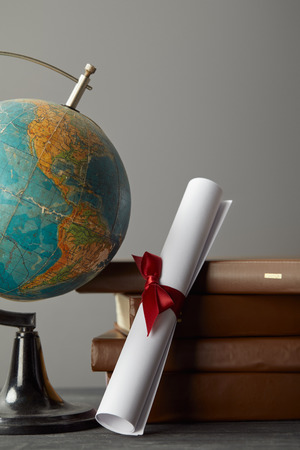Brown books, globe and diploma with red ribbon on grey Фото со стока