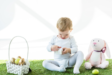 adorable kid holding white box while sitting on green grass near toy rabbit and straw basket with Easter eggs isolated on white Standard-Bild - 119798637