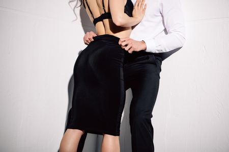 cropped view of man undressing woman on white