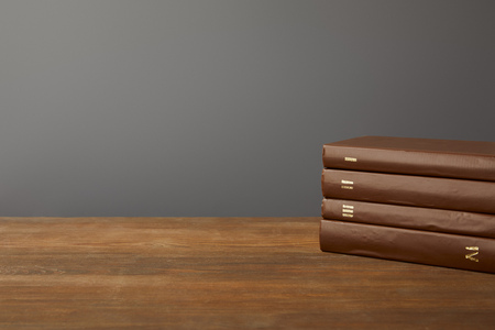 Four brown books on textured wooden surface on grey Stockfoto