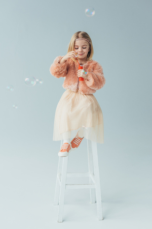 adorable kid in faux fur coat and skirt sitting on highchair and blowing soap bubbles