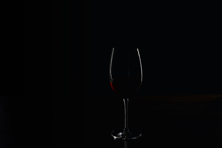 Silhouette of glass of burgundy red wine on black