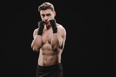 strong shirtless muscular sportsman in bandages doing block isolated on black