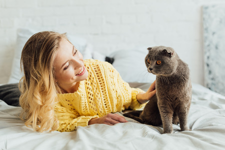 beautiful smiling girl in knitted sweater stroking scottish fold cat while lying in bed at home Фото со стока