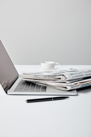 selective focus of laptop with blank screen near newspapers, pen and cup on grey 스톡 콘텐츠