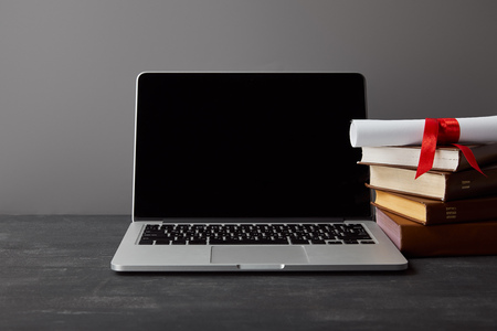 Laptop with blank screen, diploma and books isolated on grey