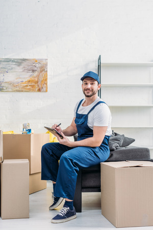 mover in uniform looking at camera while sitting near cardboard boxes with clipboard in apartment
