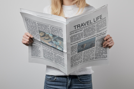 cropped view of woman holding travel newspapers isolated on grey Stock Photo