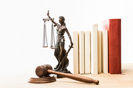 figurine with scales of justice, brown gavel and books on wooden table isolated on white