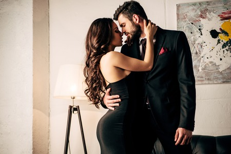 attractive woman in black dress hugging with passionate man in suit 스톡 콘텐츠