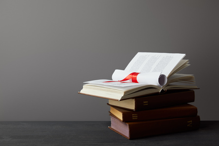 Books and diploma with red ribbon on dark surface on grey