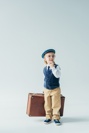 dreamy kid in retro vest and cap holding suitcase and looking away on grey background Imagens - 119800072
