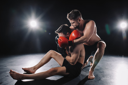 strong mma fighter in boxing gloves doing chokehold to another sportsman on floor