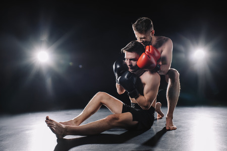 strong mma fighter in boxing gloves doing painful chokehold to another sportsman on floor 스톡 콘텐츠