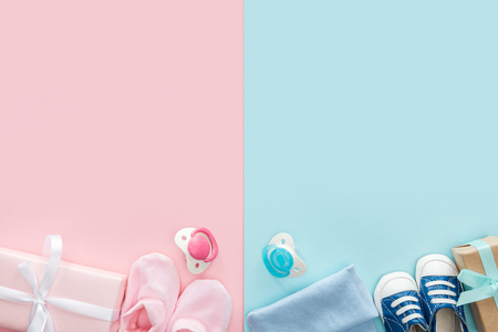 top view of pacifiers, gifts, hat, booties, sneakers on pink and blue background Stockfoto