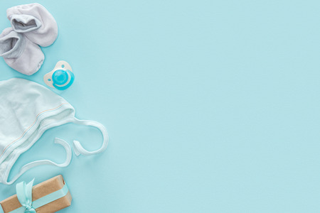 top view of pacifier, gift, bonnet, booties on blue background with copy space 스톡 콘텐츠