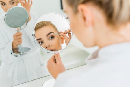 selective focus of attractive woman plucking eyebrows with tweezers in bathroom Stock Photo