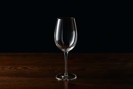 Empty wine glass on wooden surface isolated on black