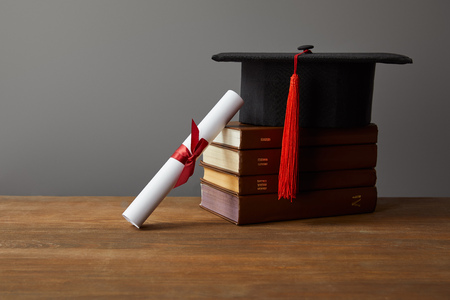 Diploma, academic cap and books on wooden surface isolated on grey
