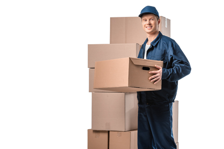 handsome mover in uniform carrying cardboard box and looking at camera isolated on white with copy space