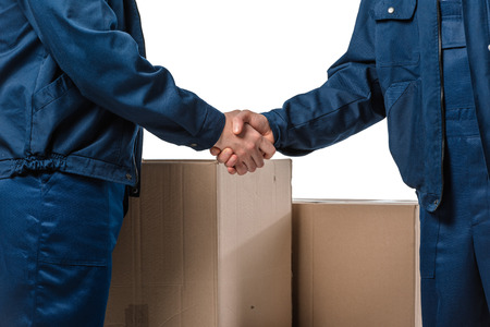 cropped view of two movers in uniform shaking hands near cardboard boxes isolated on white 스톡 콘텐츠