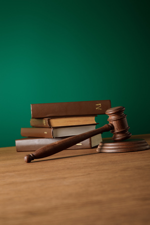 volumes of brown books in leather covers and gavel on wooden table on dark green background