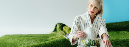 panoramic shot of beautiful stylish blonde girl sitting on artificial grass Banque d'images