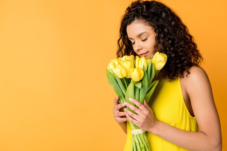 attractive curly african american woman smelling yellow tulips isolated on orange
