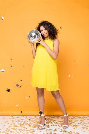 beautiful curly african american girl holding disco ball near shiny confetti stars on orange