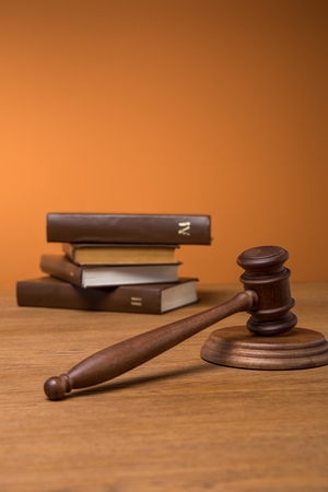 selective focus of volumes of brown books in leather covers and gavel on wooden table on orange background 版權商用圖片