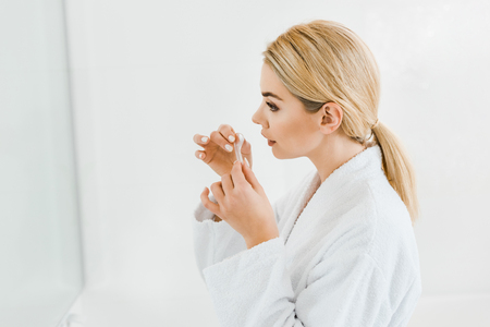beautiful and blonde woman in white bathrobe applying eye patches in bathroom