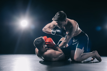 shirtless strong mma fighter in boxing gloves standing on knees above opponent and punching him with elbow