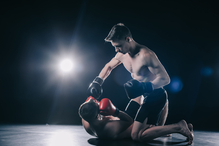 shirtless strong mma fighter in boxing gloves standing on knees above opponent and punching him