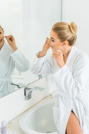 selective focus of attractive and blonde woman in white bathrobe brushing teeth with dental floss Фото со стока