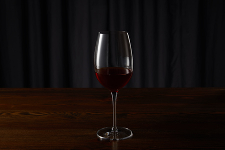 Glass with red wine on wooden surface on dark 写真素材