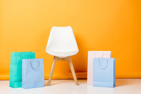 chair near blue, white and turquoise shopping bags on orange