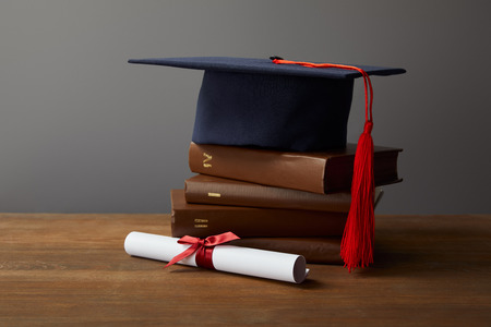 Diploma, academic cap and books on wooden surface on grey 写真素材 - 119807221