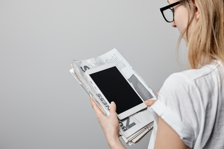 cropped view of woman in glasses holding digital tablet with blank screen and newspapers isolated on grey