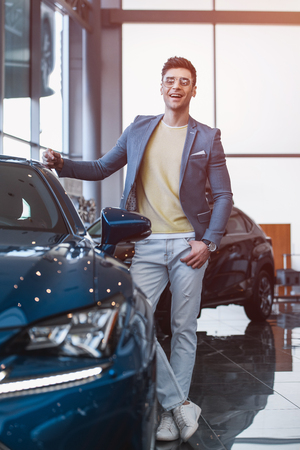 selective focus of cherful man in glasses standing near automobile with crossed legs in car showroom Stok Fotoğraf - 119867726