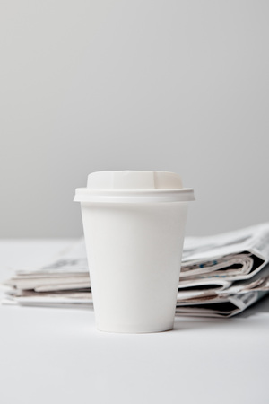 selective focus of paper cup near newspapers on grey
