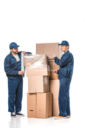 two movers wrapping cardboard boxes with roll of stretch film on white