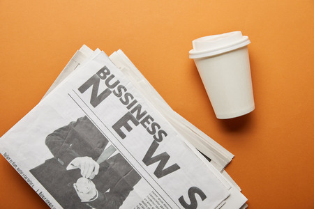 top view of business newspaper near paper cup with drink on orange