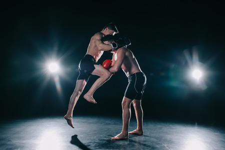 shirtless muscular mma fighter in boxing gloves kicking another with knee Archivio Fotografico - 119868929