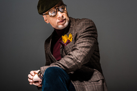 trendy and pensive mature man in cap and glasses on grey Фото со стока