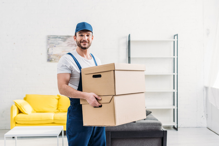 handsome mover in uniform looking at camera while carrying cardboard boxes in apartment with copy space Banque d'images
