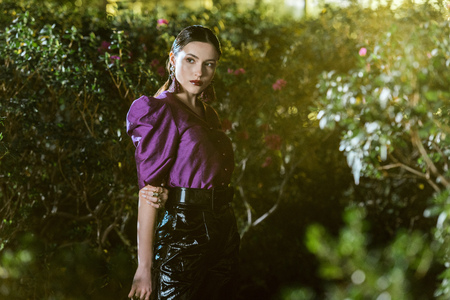 Pensive girl in purple blouse and leather pants posing in botanical garden Stock Photo