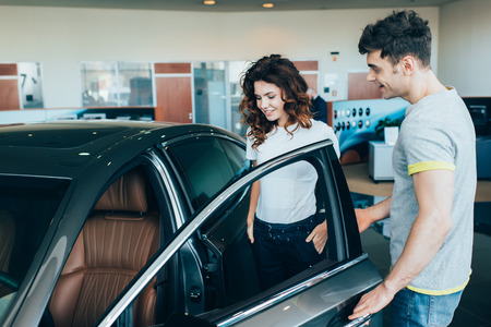selective focus of handsome man standing near attractive woman while opening car door